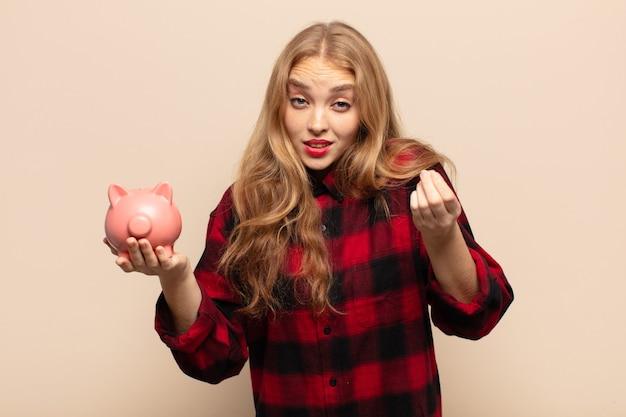 Donna bionda che fa un gesto di denaro o di denaro, dicendoti di pagare i tuoi debiti!