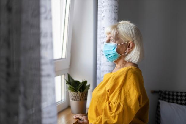 Donna bionda in quarantena maschera in isolamento a casa per epidemia di virus. rimanere a casa concetto