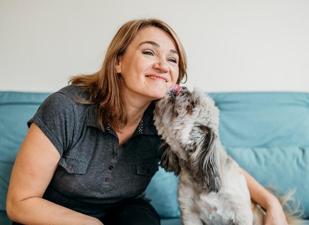Donna bionda che petting carino cagnolino