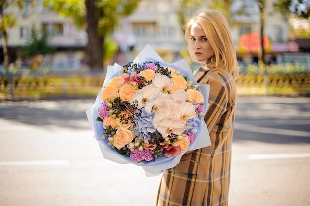Donna bionda in cappotto scozzese che tiene un grande mazzo adorabile di fiori contro la città
