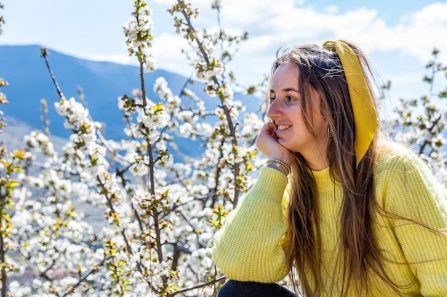 Donna bionda in posa in uno sfondo di fiori di ciliegio. valle del jerte. extremadura, spagna.