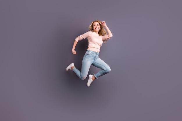 Donna bionda in posa in un maglione contro il muro viola