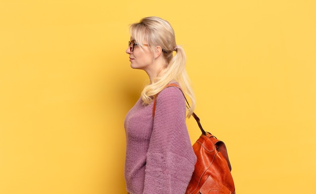 Donna bionda sulla vista di profilo che cerca di copiare lo spazio davanti, pensare, immaginare o sognare ad occhi aperti