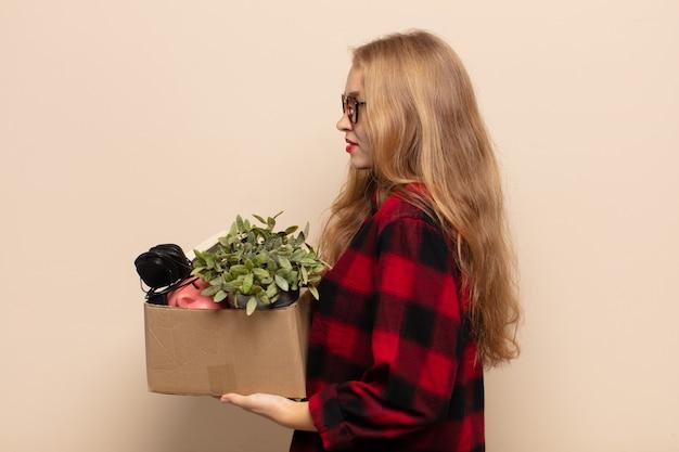 Donna bionda in vista di profilo che cerca di copiare lo spazio davanti a sé, pensando, immaginando o sognando ad occhi aperti