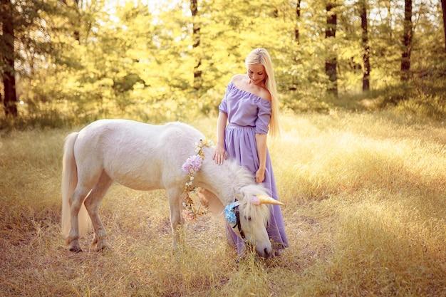 Donna bionda in vestito viola che abbraccia unicorno bianco