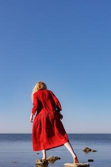 Donna bionda in un lungo abito di lino rosso in piedi in mare al mattino.