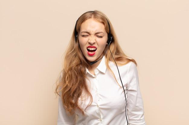 Donna bionda che grida in modo aggressivo, sembra molto arrabbiata, frustrata, oltraggiata o infastidita, grida di no