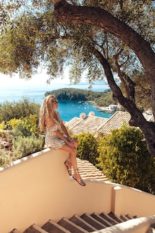 Donna bionda che si siede sulle scale con la vista di mare stupefacente dietro