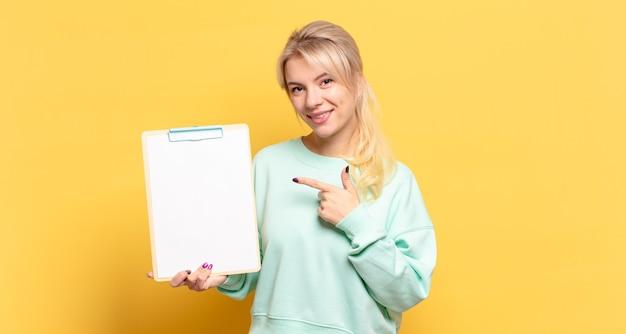 Donna bionda che sorride allegramente, sentendosi felice e indicando il lato e verso l'alto, mostrando l'oggetto nello spazio della copia