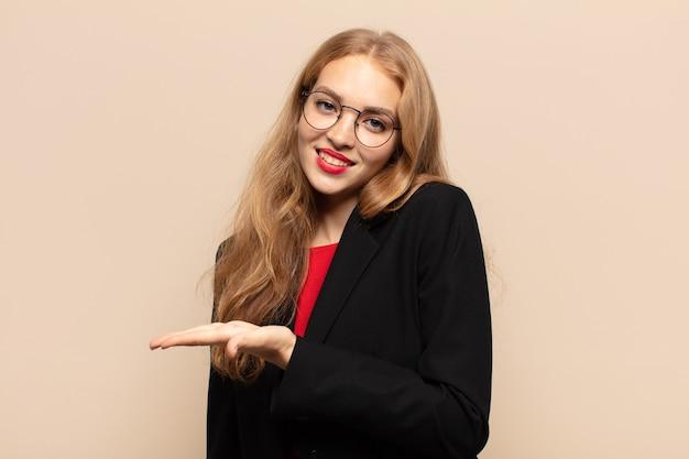 Donna bionda che sorride allegramente, sentendosi felice e mostrando un concetto nello spazio della copia con il palmo della mano