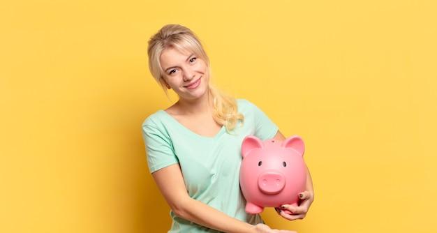 Donna bionda che sorride allegramente, si sente felice e mostra un concetto nello spazio della copia con il palmo della mano
