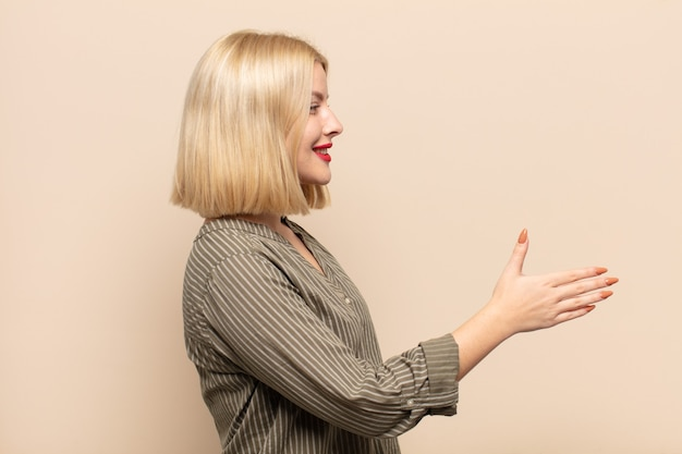 Donna bionda sorridente, salutandoti e offrendoti una stretta di mano per concludere un affare di successo, concetto di cooperazione