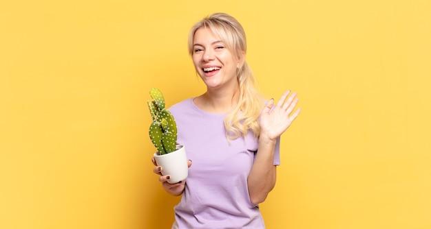 Donna bionda che sorride allegramente e allegramente, agitando la mano, accogliendoti e salutandoti, o salutandoti