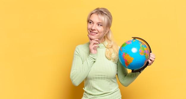 Donna bionda sorridente felicemente e fantasticando o dubitando, guardando al lato