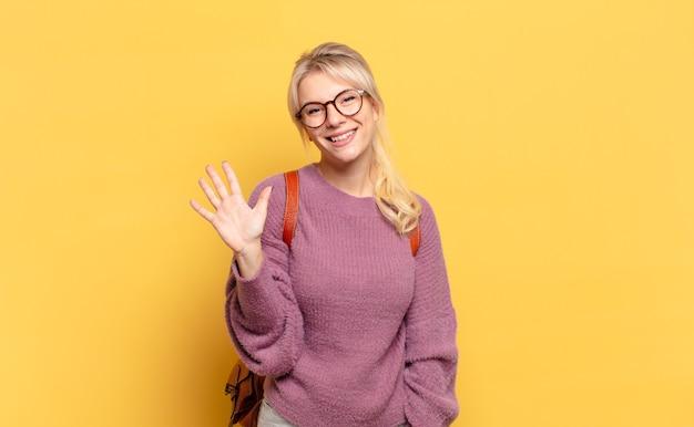 Donna bionda che sorride e sembra amichevole, mostrando il numero cinque o quinto con la mano in avanti, contando alla rovescia