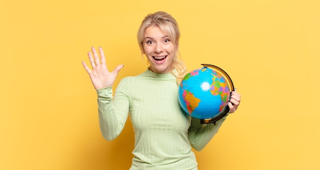 Donna bionda sorridente e dall'aspetto amichevole, che mostra il numero cinque o il quinto con la mano in avanti, conto alla rovescia