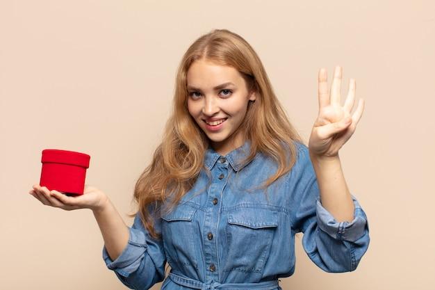 Donna bionda che sorride e sembra amichevole, mostrando il numero quattro o quarto con la mano in avanti, conto alla rovescia