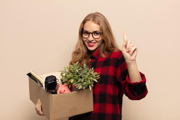 Donna bionda sorridente e dall'aspetto amichevole, mostrando il numero uno o il primo con la mano in avanti, il conto alla rovescia