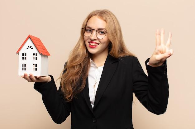 Donna bionda sorridente e guardando amichevole, mostrando il numero tre o terzo con la mano in avanti, conto alla rovescia