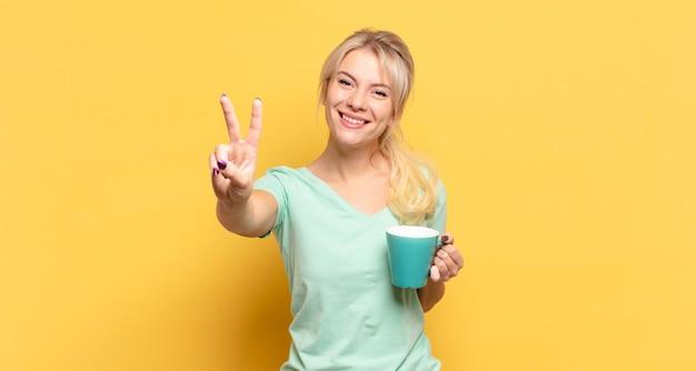 Donna bionda che sorride e sembra amichevole, mostrando il numero due o il secondo con la mano in avanti, il conto alla rovescia
