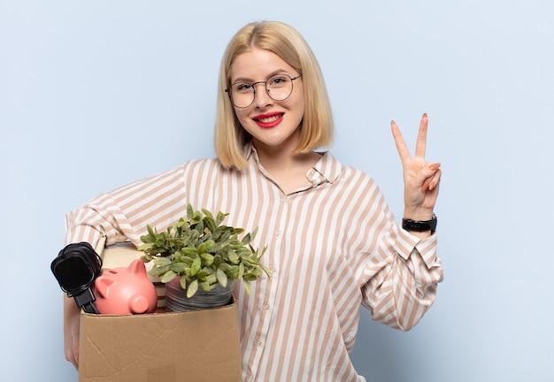 Donna bionda che sorride e sembra amichevole, mostrando il numero due o il secondo con la mano in avanti, conto alla rovescia