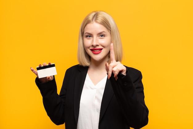 Donna bionda che sorride con orgoglio e sicurezza facendo posare trionfante il numero uno, sentendosi come un leader