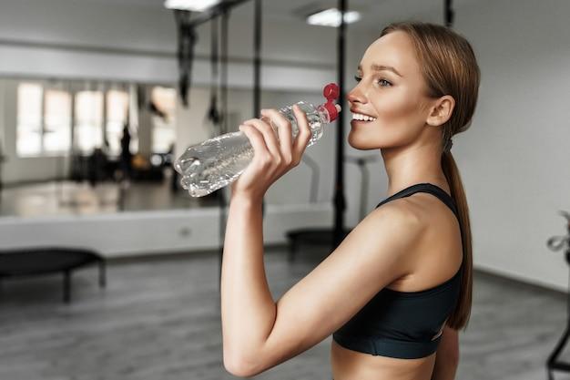 Donna bionda in abbigliamento sportivo che beve acqua dopo l'allenamento in una moderna palestra