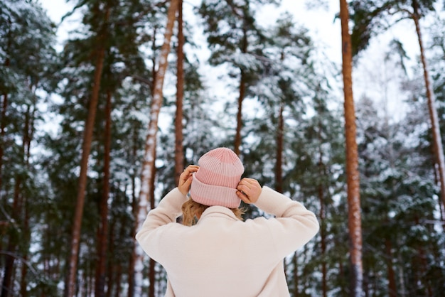 Donna bionda che sta indietro e che guarda lago magico nel paesaggio montuoso del paese.
