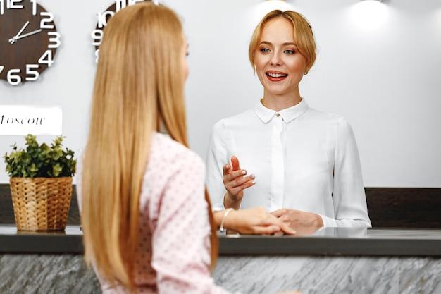 Donna bionda in piedi alla reception dell'hotel reception si chiuda