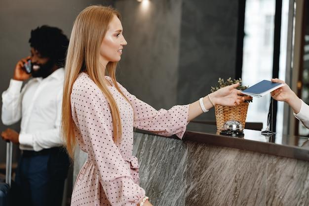 Donna bionda in piedi alla reception dell'hotel reception
