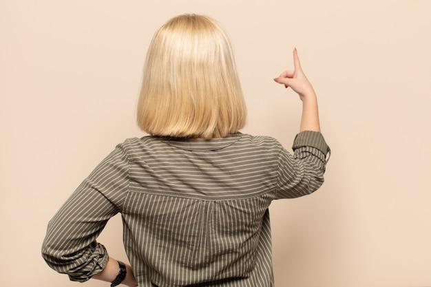 Donna bionda in piedi e indicando un oggetto sullo spazio della copia, vista posteriore