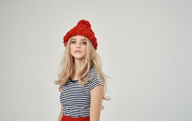 Donna bionda in t-shirt a righe e ritratto di cappello rosso su sfondo chiaro vista ritagliata
