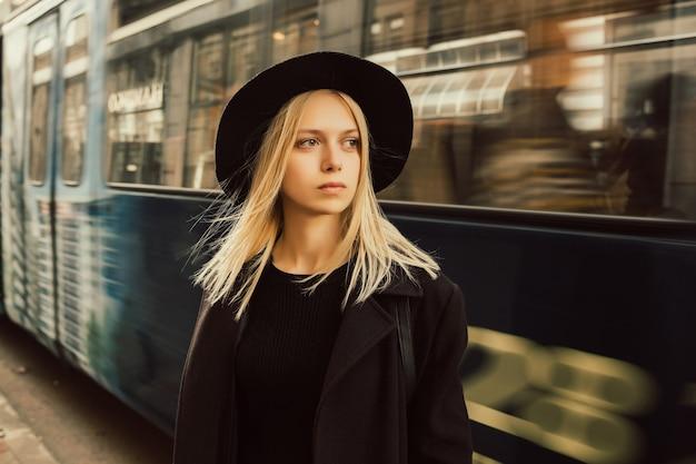 Donna bionda in elegante cappotto nero e cappello andando a lavorare