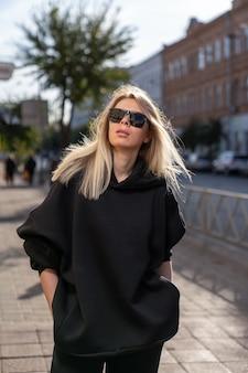 Donna bionda in occhiali da sole che indossa una felpa con cappuccio nera cammina per la città