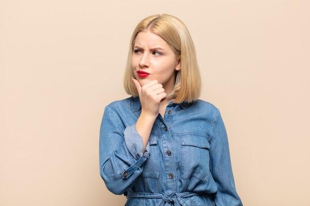 Donna bionda che pensa, che si sente dubbiosa e confusa, con diverse opzioni