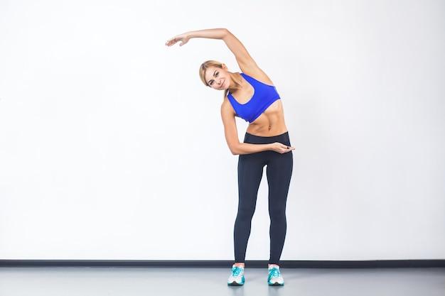 Lato di inclinazione della donna bionda, facendo esercizio di fitness, allenamento. foto in studio