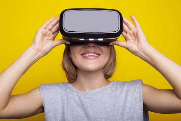 Donna bionda che indossa un auricolare per realtà virtuale su una parete gialla dello studio sorridendo a trentadue denti