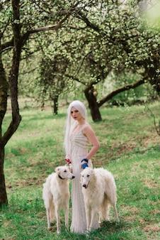 Donna bionda in vestito bianco che gioca con il suo cane wolfhound russo in giardino.