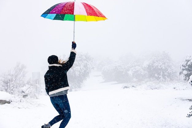 Donna bionda con un ombrello colorato che viene spazzata via dal vento con il suo ombrello paesaggio innevato.