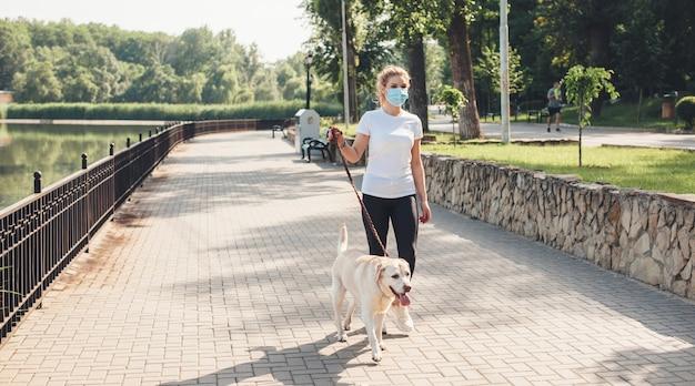 Donna bionda con mascherina medica sta camminando con il suo cane nel parco vicino a un lago