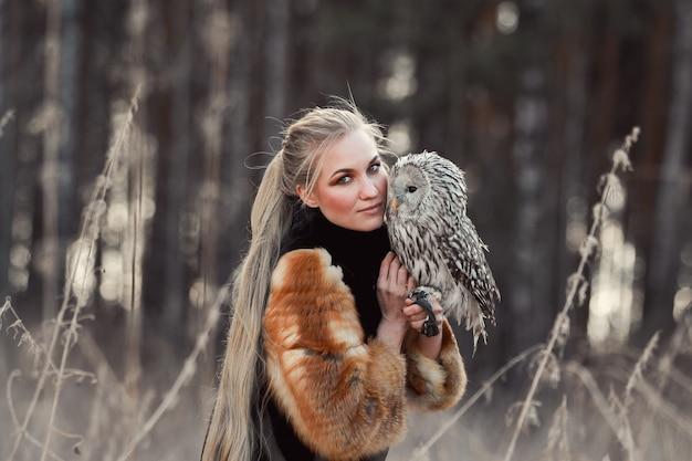 Donna bionda con un gufo in mano cammina nei boschi in autunno e in primavera. ragazza capelli lunghi, ritratto romantico con gufo. foto di moda artistica, bel trucco beautiful