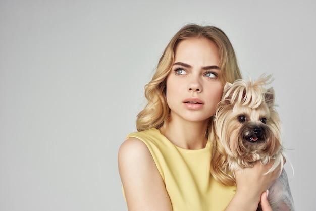 La bionda con un vestito giallo si diverte con un cagnolino tagliata vista la moda
