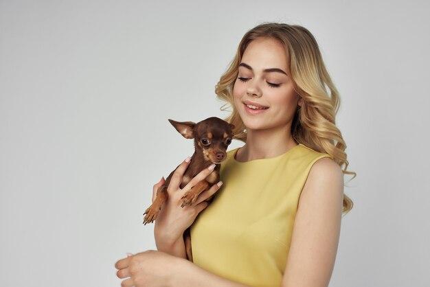 La bionda in un vestito giallo si diverte con uno studio di sfondo chiaro per cani di piccola taglia