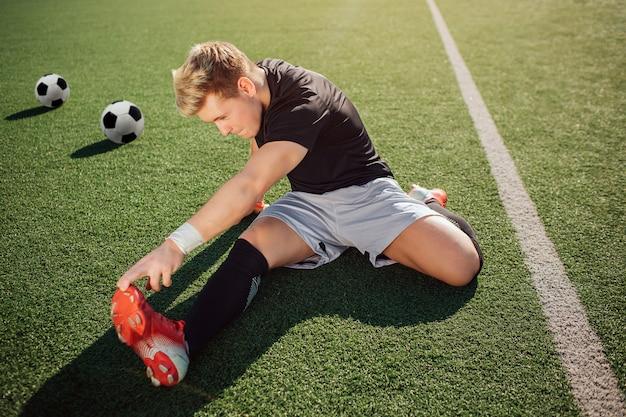 Giovane allungamento biondo del giocatore di football americano fuori su prato inglese. raggiunge i piedi con la mano. il ragazzo è concentrato sull'esercizio. due palloni da calcio dietro di lui.