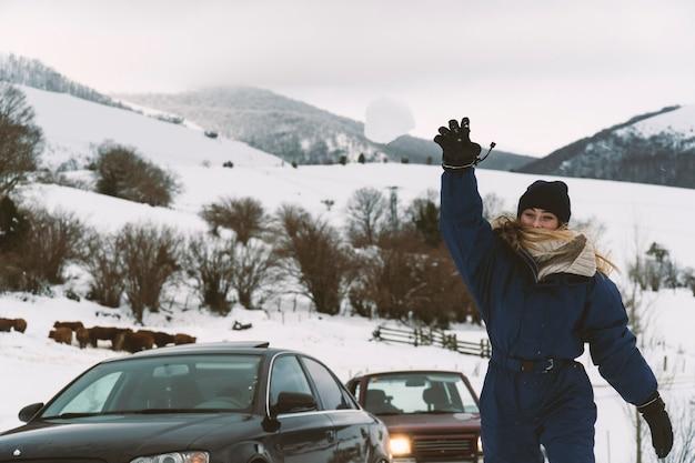 Ragazza bionda che lancia una palla di neve alla telecamera in montagna