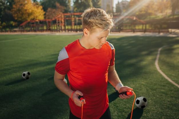Mani bionde di iin della corda di salto della tenuta del giovane. lui lo guarda. guy stare sul prato fuori. il sole splende. le palle circondano il giovane.