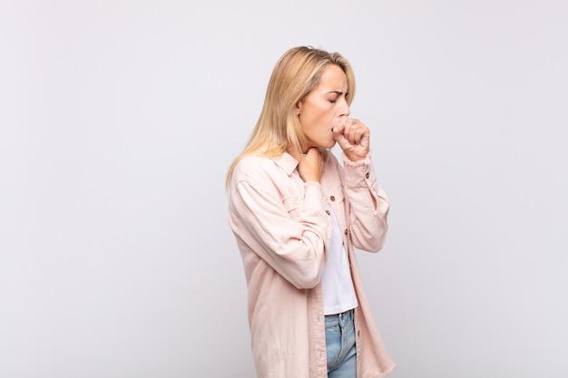 Giovane donna graziosa bionda che tossisce