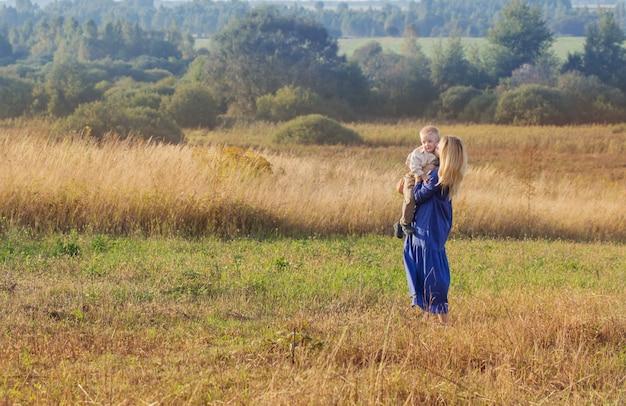 Giovane donna bionda in abito blu in campo al tramonto