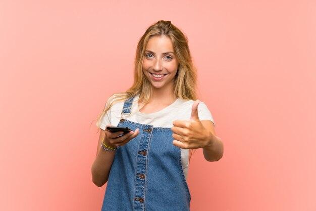 Giovane donna bionda con un telefono cellulare sopra la parete rosa isolata con i pollici su perché è successo qualcosa di buono