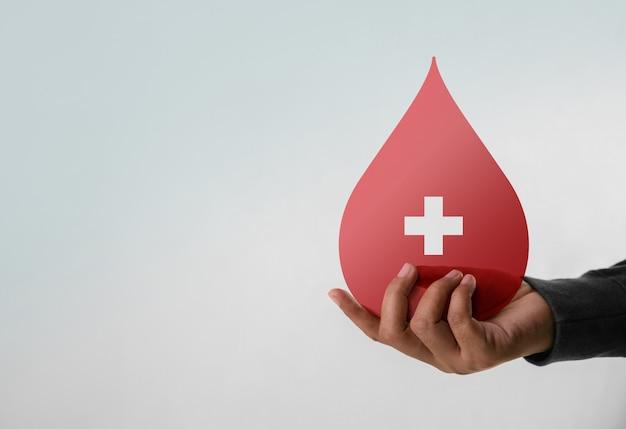 Concetto di donazione di sangue. aiuto, cura, amore, supporto. mano che tiene una goccia rossa e un segno di croce